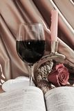 Gratitude and hope, symbols. The Bible, a candle, a rose, a glass of red wine and a heart shaped object, on a beautiful background, as symbols of gratitude and Stock Images