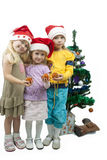 With Gratitude to our parents. Three young little caucasian blond girls standing together near christmas tree holding gifts and smiling sincerely.isolated over Stock Photo