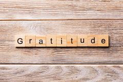 Gratitude word written on wood block. gratitude text on wooden table for your desing, concept