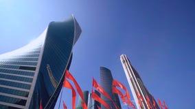 Grattacieli del distretto dei busineess di intrenational di Mosca con le bandiere rosse d'ondeggiamento stock footage