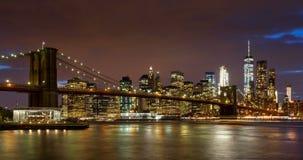 Grattacieli, ponte di Brooklyn ed East River finanziari del distretto del Lower Manhattan con passare le nuvole alla penombra Man