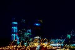 Grattacieli vaghi Costruzioni a più piani alla notte, finestre illuminate Città al neon moderna a velocità dell'automobile Immagini Stock
