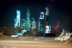 Grattacieli vaghi Costruzioni a più piani alla notte, finestre illuminate Città al neon moderna a velocità dell'automobile, fondo Immagini Stock