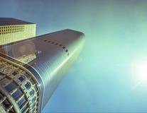 Grattacielo brillante con il fondo luminoso del cielo blu del sole Fotografia Stock Libera da Diritti