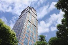 Grattacielo contro un cielo nuvoloso blu, Shanghai, Cina Fotografia Stock