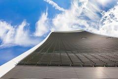 Grattacielo curvo contro cielo blu Immagini Stock Libere da Diritti