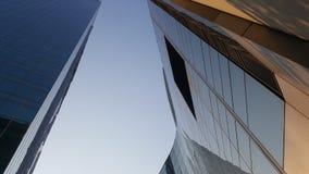 Grattacielo di vetro della facciata sul chiaro fondo del cielo blu fotografia stock