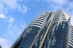 Grattacielo su un cielo nuvoloso del fondo Immagine Stock