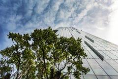 Grattacielo urbano alto in distretto finanziario con le nuvole drammatiche lunatiche Immagine Stock