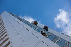 Gratte-ciel de nettoyage dehors avec une grue - lavage de fenêtre photographie stock libre de droits