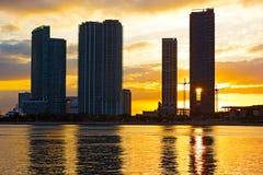 Gratte-ciel près du bord de mer avec le coucher du soleil lumineux au fond Photographie stock