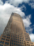 Gratte-ciel sous un ciel bleu nuageux Photo stock