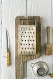 Grattugia, tuffatore, filtro e coltello sul verticale di legno bianco della tavola immagine stock