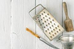 Grattugia, tuffatore, filtro e coltello sulla vista di legno bianca del piano d'appoggio fotografie stock libere da diritti