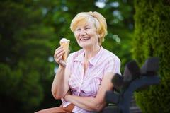 Grau-haarige Frau, die mit Eiscreme auf Bank im Park sich entspannt Lizenzfreies Stockfoto