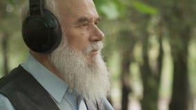 Grau-haariger älterer Mann hört Musik in den Kopfhörern stock video