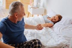 Grau-haariger Ehemann, der Hand seiner Frau nachdem dem Aufwachen nimmt stockbild