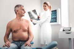 Grau-haariger Mann, der junge blond-haarige Krankenschwester betrachtet lizenzfreies stockbild