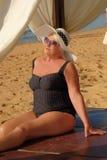 Grau-köpfige ältere Frau, die auf dem Strand sich entspannt Eleganter Hut und lizenzfreie stockfotografie