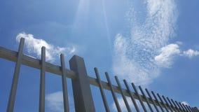 Grau malte Metallzaun mit Hintergrund des blauen Himmels Stockfoto