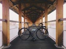 Grau-schwarzes fixie Fahrrad im hölzernen Weg Stockfoto