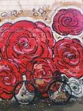 Grau-schwarzes fixie Fahrrad vor der Wand mit hellem Rot blüht Graffiti Lizenzfreies Stockbild