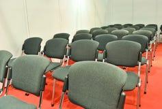 Grau sitzt rotem Fußboden vor lizenzfreie stockfotografie
