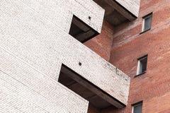 Grau und Wände des roten Backsteins mit Balkon und Fenstern Lizenzfreies Stockbild