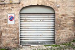 Grau verrostete Metalltor in der alten Backsteinmauer, Hintergrund Stockbild