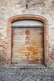 Grau verrostete Metalltor in der alten Backsteinmauer, Hintergrund Lizenzfreies Stockbild