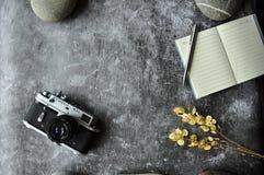 Graue Abstraktionshintergrundtabelle für Standort Details auf dem Tisch: Notizblock, Stift, Kamera, trockene Blumen Hintergrundre lizenzfreies stockbild