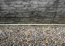 Graue Backsteinmauer auf Steinboden Lizenzfreie Stockfotografie