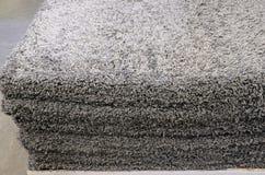 Graue Badmatten des Stapels, welche die Badmatten stapeln, gestapelt auf einander stockbild