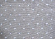 Graue Baumwollserviette mit Herzen verzierter Hintergrund für Valentinsgrußtag Lizenzfreies Stockfoto