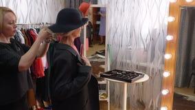 Graue behaarte ältere Frau, die neuen Mantel im Ausstellungsraumatelier versucht Kleidungsdesigner, der hilft, Jacke und Hut für  stock footage