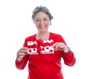 Graue behaarte Frau des smiley im Rot, das Geschenk lokalisiert auf Whit hält Lizenzfreies Stockfoto