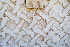 Graue Beschaffenheit ist eine konkrete alte, geschnitzte, konvexe Wand des Zementes mit Verzierungen und Muster Lizenzfreies Stockfoto
