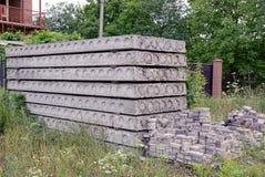 Graue Betonblöcke und Pflastersteine im Gras nahe der Hausmauer Lizenzfreie Stockfotografie
