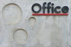 Graue Betonmauer mit Bürotext-Hintergrundbeschaffenheit Stockfoto