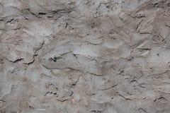 Graue Betonmauer mit großen Anschlägen des Gipses Stockfotografie