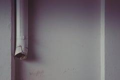Graue Betonmauer mit Wasserleitung Stockfotos