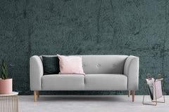 Graue Couch mit Kissen in der dunklen Wohnung Innen mit strukturierter Wand Reales Foto stockbild