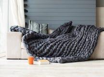 Graue Decke der Merinowolle, die auf weißem Sofa mit einer orange Schale liegt Lizenzfreie Stockbilder
