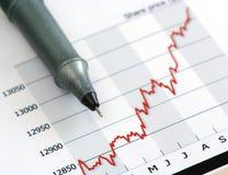 Graue Feder auf weißem wachsendem Aktienkursdiagramm Stockbild