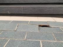 Graue Fliesen mit Sprüngen, Boden stürzt, gebrochene Hausprobleme ein lizenzfreie stockfotos