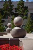 Graue Granitbälle mit Sockeln als Dekoration Lizenzfreies Stockfoto