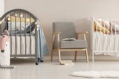 Graue h?lzerne Krippe im modernen skandinavischen Babyschlafzimmerinnenraum stockfotografie