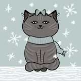 Graue Katze mit blauem Schal sitzt auf dem Schnee unter fallenden Schneeflocken Lizenzfreies Stockbild