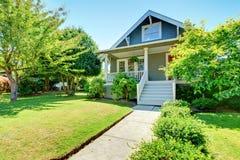 Graue kleine alte amerikanische Hausfront außen mit weißem Treppenhaus. Lizenzfreies Stockfoto