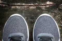 Graue Laufschuhe auf einem grungy Bretterboden Stockbilder